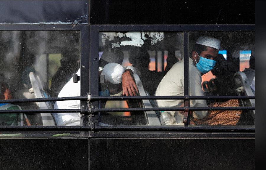 Karantina merkezlerine götürülmek üzere otobüste bekleyen Müslümanlar.