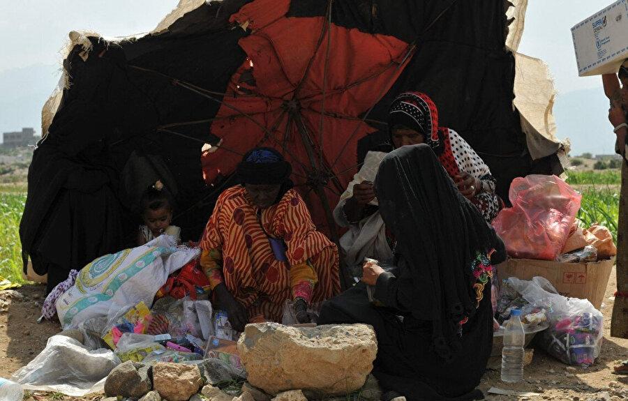 Yemenli kadınlar derme çatma çadırın altında hazırladıkları atıştırmalıkları satmaya çalışıyor.