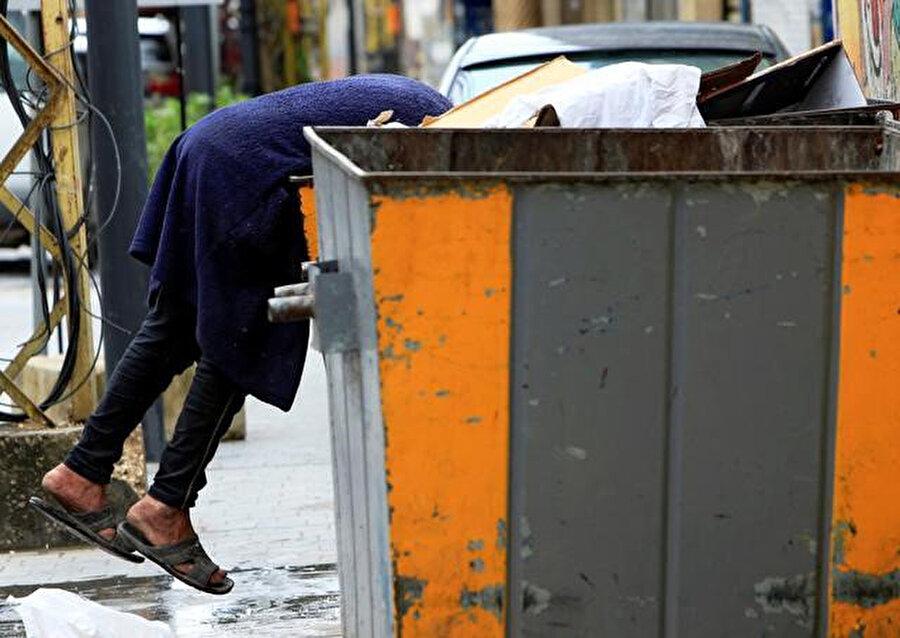 Bir hafta önce çekilen bu fotoğrafta çöpten yiyecek arayan bir Lübnanlı görülüyor.