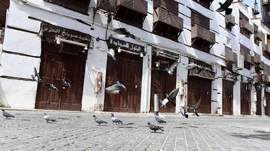 Suudi Arabistan'ın Cidde kentinde sokağa çıkma yasağı dolayısıyla kapatılan dükkanların önünde güvercinler uçuşurken görülüyor.