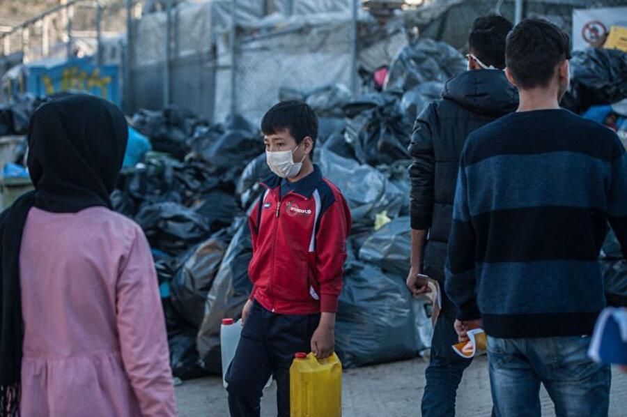 Yunanistan'daki kapasitesinin üzerinde binlerce kişiyi barındıran kamplarda maskeyle korunmaya çalışan mülteciler.