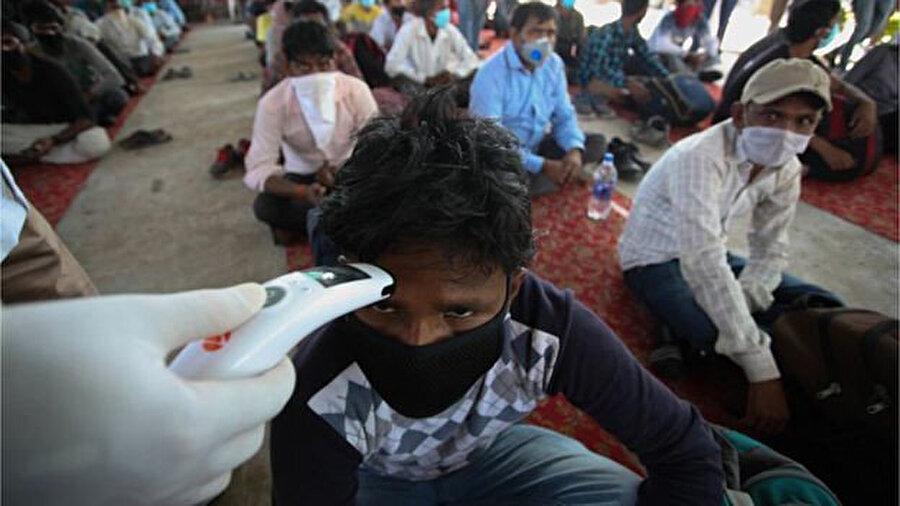 Karantina merkezinde kalan işçiler sağlık kontrolünden geçirilirken görülüyor.