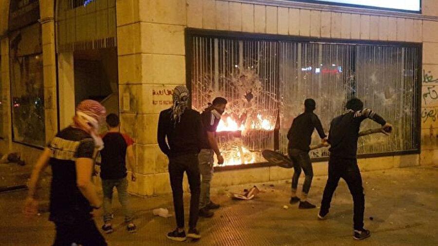 Yoldan söktükleri trafik levhaları ile banka şubelerine zarar veren göstericiler şubeleri ateşe verdi.