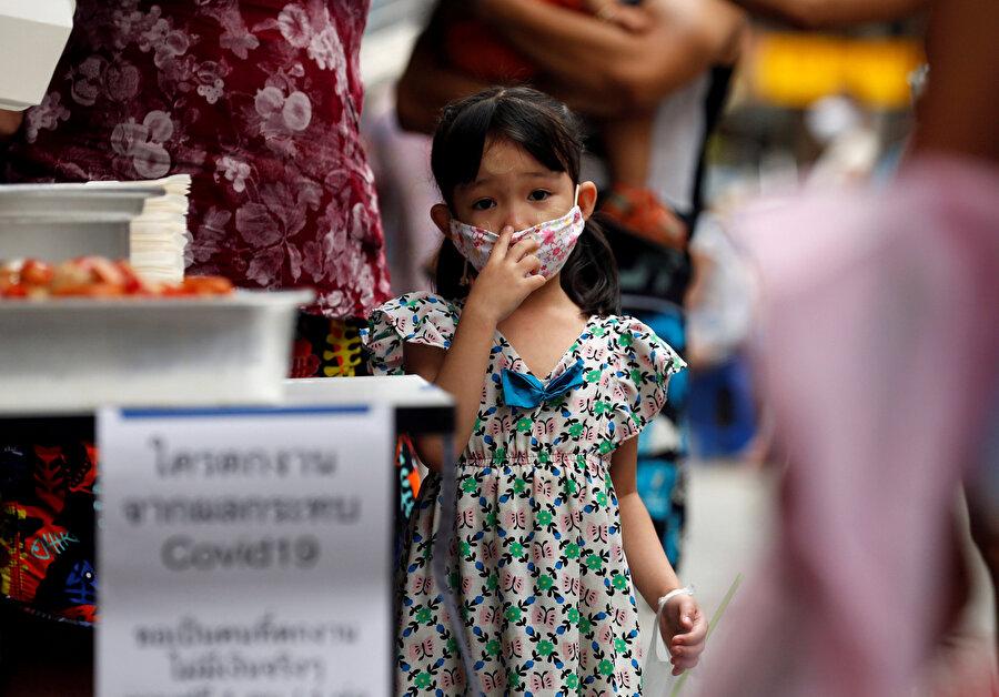 Myanmarlı bir kız çocuğu maske takarken görünüyor.