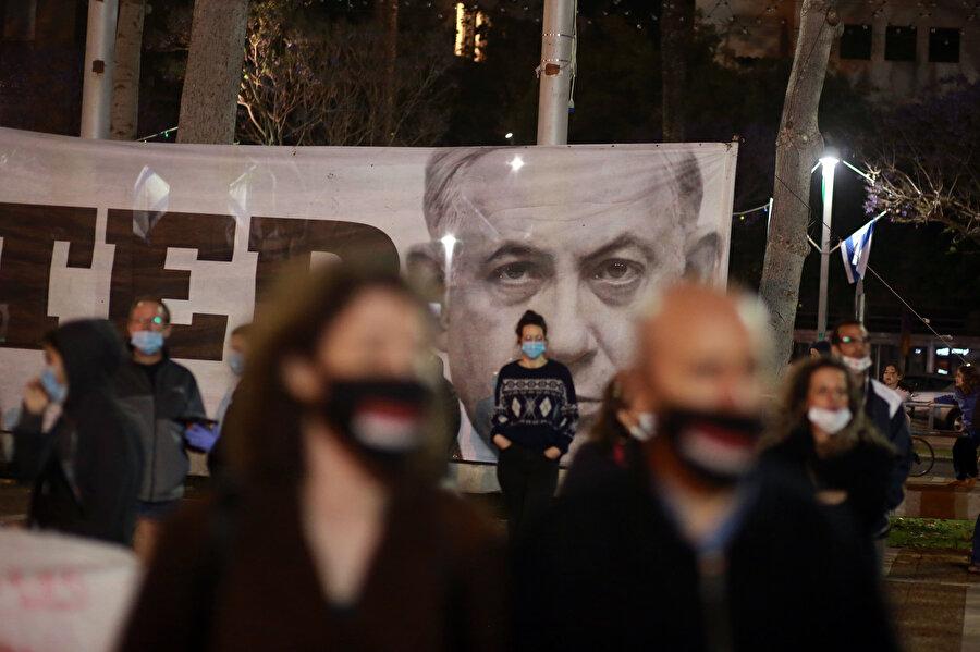 Maske takan İsraillilerin arkasında Binyamin Netanyahu'nun afişi görünüyor.