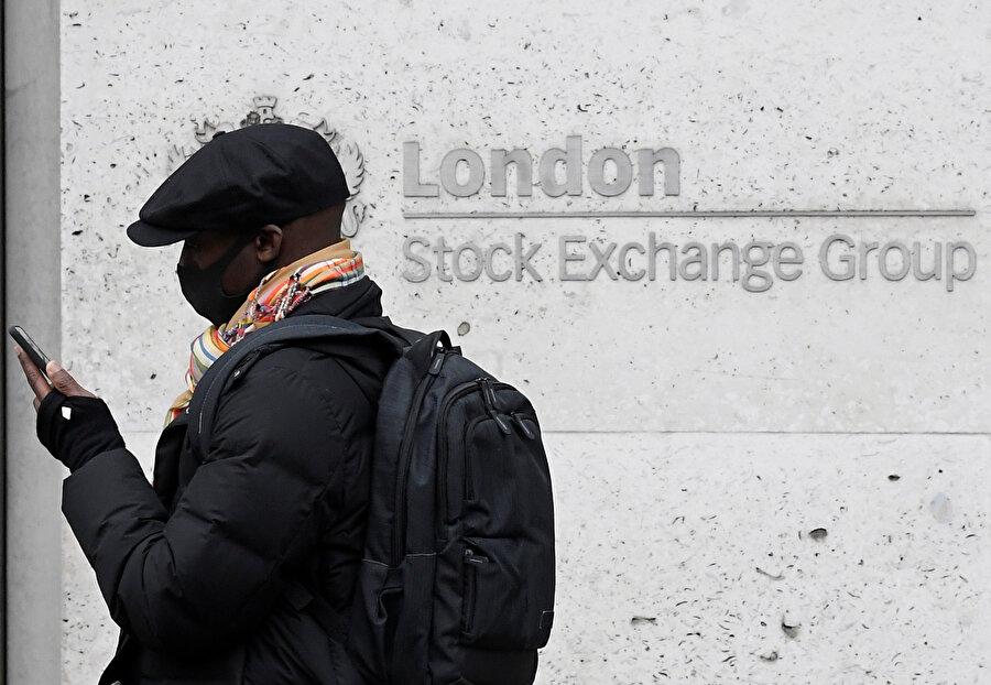 Londra Borsası'nın önünde bir vatandaş telefonuna bakarken görünüyor.