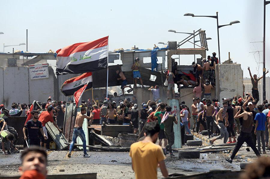 Polis bariyerini aşmaya çalışan göstericiler.