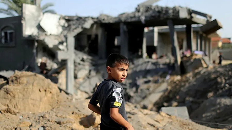 İsrail saldırısında yıkılan evlerinin enkazına bakan Filistinli bir çocuk.