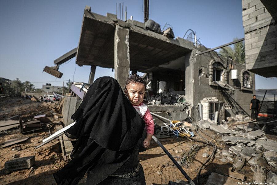 İsrail saldırılarında evi yıkılan bir anne kucağında çocuğuyla enkaz altında kalanları kurtarmaya gelirken görülüyor.