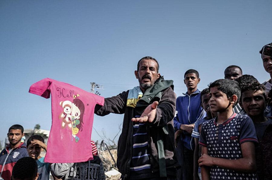 İsrail'in Gazze'ye düzenlediği saldırlarda yaşamını yitiren çocukların kıyafetlerini gösteren bir yakını.