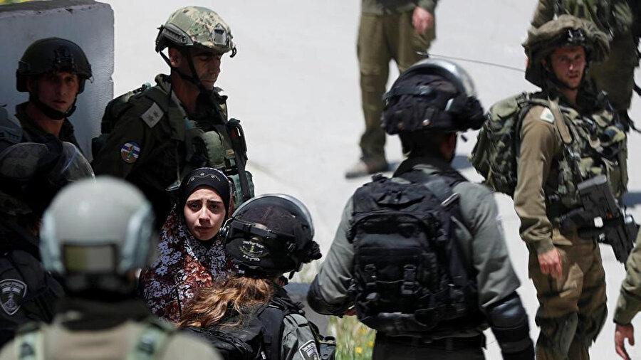İşgal altındaki Batı Şeria'da İsrail askerleri tarafından yolu kesilen Filistinli bir kadın.