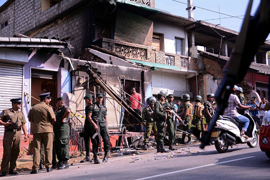 Ateşe verilen Müslümanlara ait bir evin önünde güvenlik çemberi oluşturan askerler ve olay yerine gelen vatandaşlar.