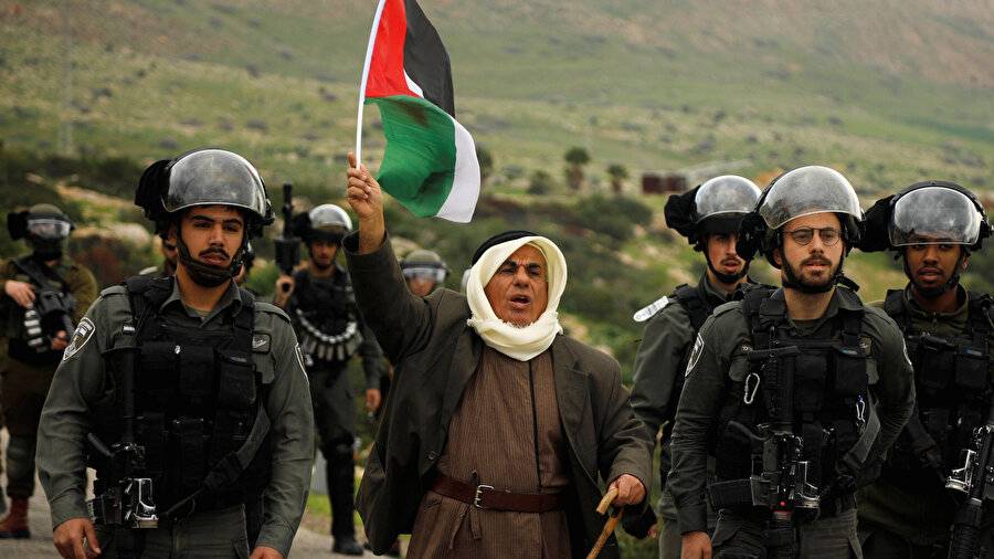 Yasa dışı İsrail yerleşimlerini ve Trump'ın sözde Orta Doğu Barış Planını protesto eden bir Filistinli, İsrail polisinin arasında kalmış halde görülüyor.