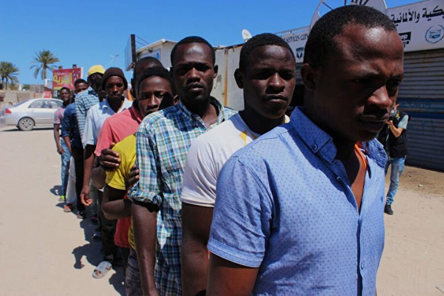 Libya'nın Misrata kentinde geçtiğimiz Ramazan ayında dağıtılan gıda yardımlarından almak için sıra bekleyen düzensiz göçmenler.