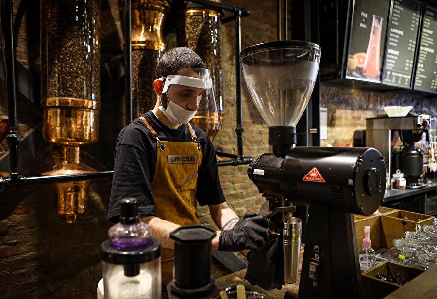 Bir çalışan kahve hazırlarken görünüyor.