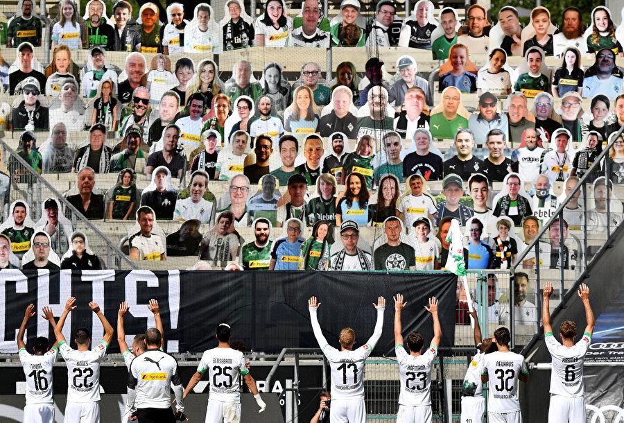 Kartondan yapılan taraftarlara futbolcular selam veriyor.
