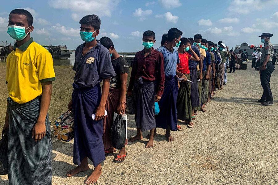 Salıverilen mahkumların koronavirüs tedbirleri kapsamında maske taktıkları görülüyor.