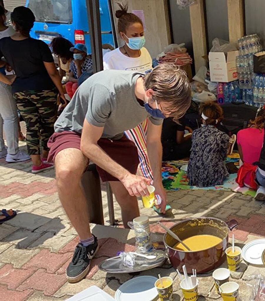 Sokakta kalan göçmenlere yemek dağıtan gönüllüler.