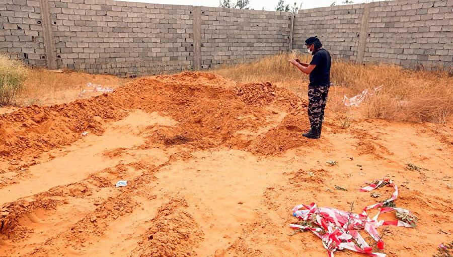 Ulusal Mutabakat Hükümetine bağlı bir güvenlik görevlisi Terhune vilayetinde ortaya çıkarılan bir toplu mezarı fotoğraf çekerken görülüyor.