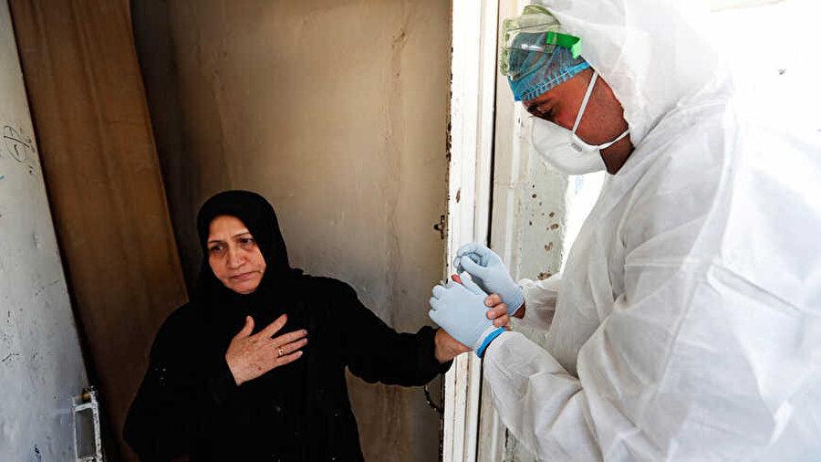 Bağdat'ta Koronavirüs testi için bir vatandaştan kan örneği alan sağlık görevlisi.