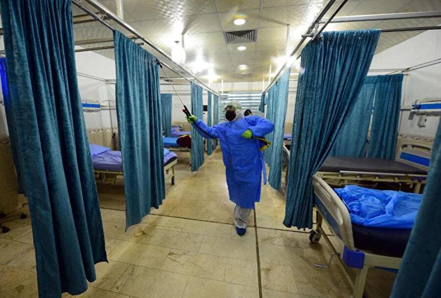 Necef'te bir hastaneyi dezenfekte eden görevliler.