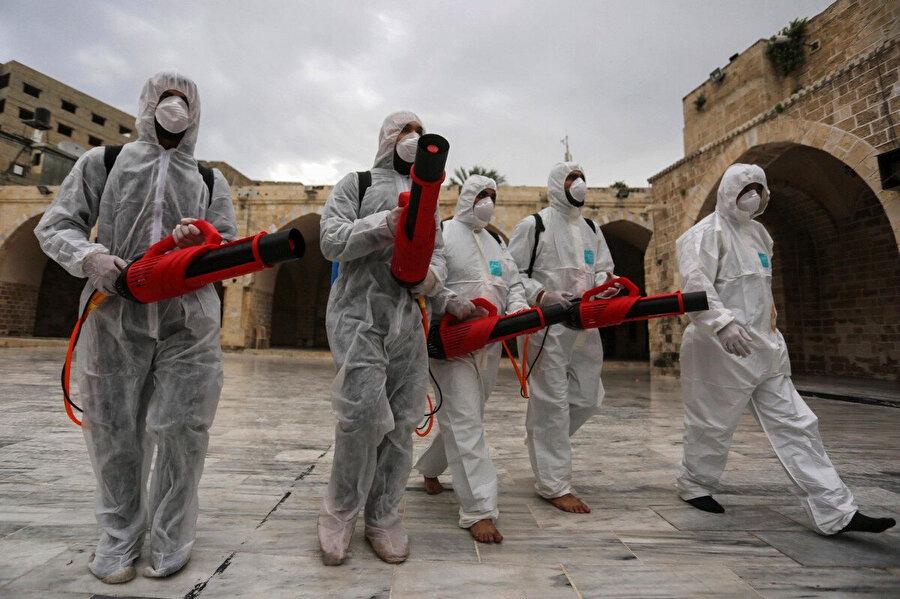 Koronavirüs tedbirleri kapsamında ibadet yerlerini dezenfekte eden Filistinli işçiler.