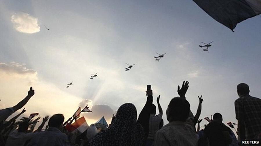Tahrir Meydanı'nın üzerinden geçen savaş uçaklarını selamlayan eylemciler.