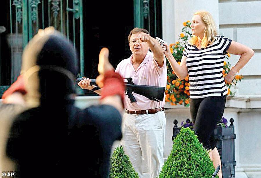 Uzun namlulu tüfek taşıyan Mark McCloskey ve tabancalı eşi Patricia, eylemcileri 'bahçeye girmeleri halinde ateş edeceklerini' söyleyerek uyardı.