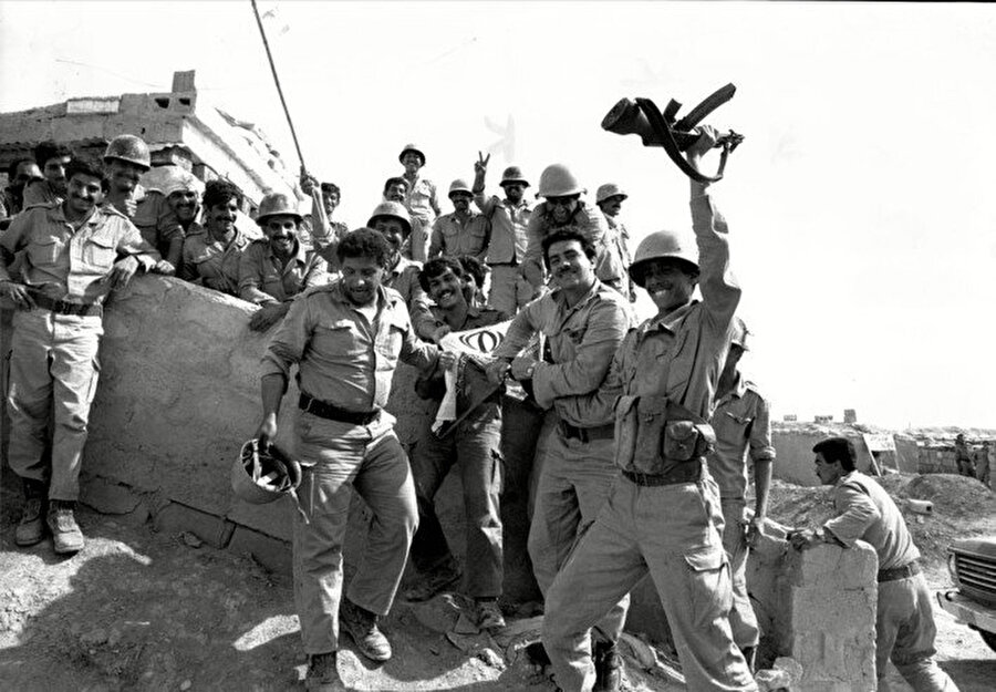 Sınırı geçen ve İran bayrağı parçalayarak kutlama yapan Iraklı askerler.