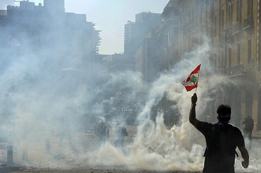 Beyrut'taki gösterilerde elinde bayrakla bir vatandaş görünüyor.