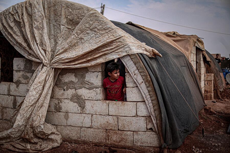 Bazı aileler, yalıtım oluşturmak için çadırların üzerine beyaz kumaş sererek ıslatıyor.