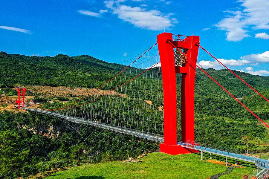 Cam köprü geçidin iki ucundaki kırmızı kulelere asılı.