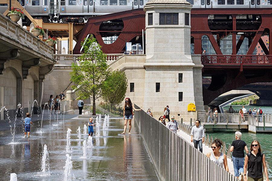 Water Plaza'daki çeşme, kullanıcıların nehrin kenarındaki su ile etkileşime girmesine olanak tanıyor.
