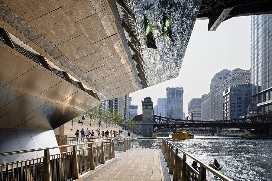 Chicago Nehri'nin köprüleri altından koyları birbirine bağlayan paslanmaz çelik saçaklı mini köprüler, hem yayaları yukarıdaki köprü güvertesinin altından geçerken koruyor hem de nehir yüzeyinin dokusunu ve ışığını yansıtıyor.