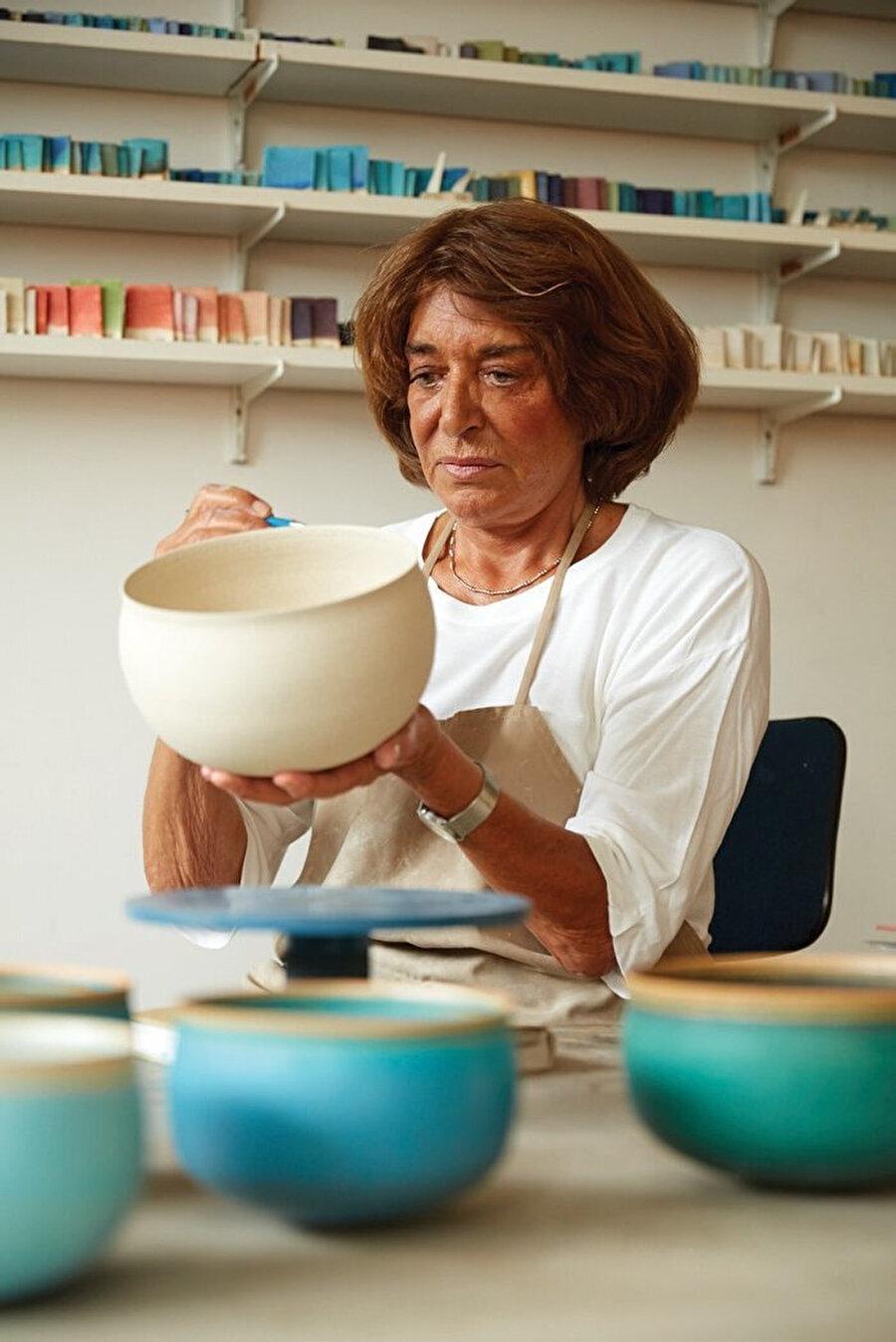 Alev Ebüzziya atölyede çanak yaparken.
