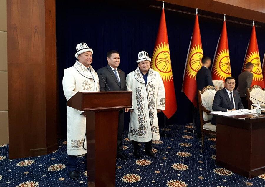 Genel Kurul'da en yaşlı milletvekilleri, eski Meclis Başkanları Dastanbek Cumabekov ile Kanat İsayev'e geleneksel Kırgız kalpağı ve kıyafeti giydirdi.