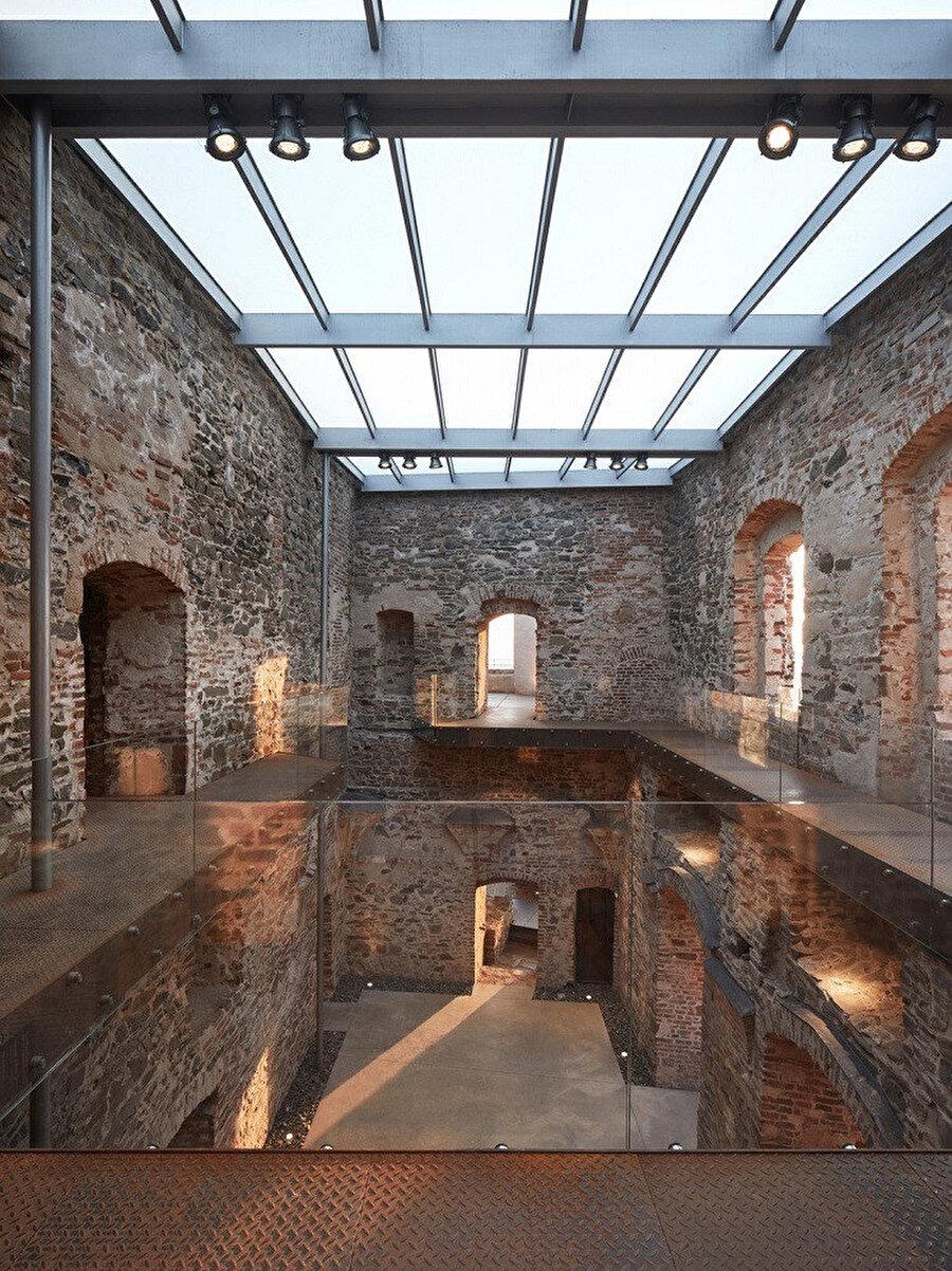 Saraya eklenen 3 ana malzeme; çelik çerçeveli cam çatı, corten çelik ara katlar ve beton zemin kat.