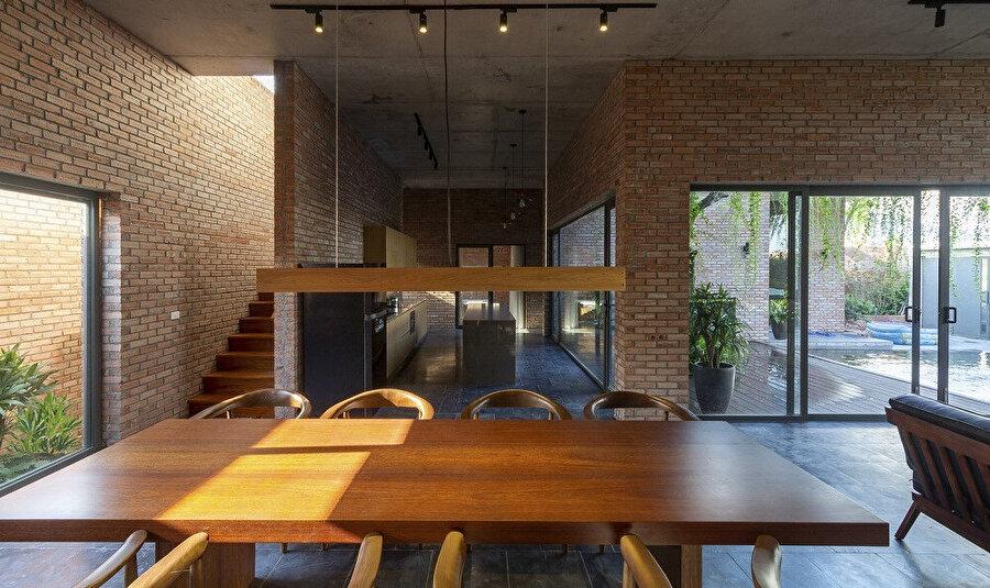 Evin mutfağı, yemek bölümü ve yaşam alanı; bölücü yapı elemanı kullanılmadan tasarlanıyor.