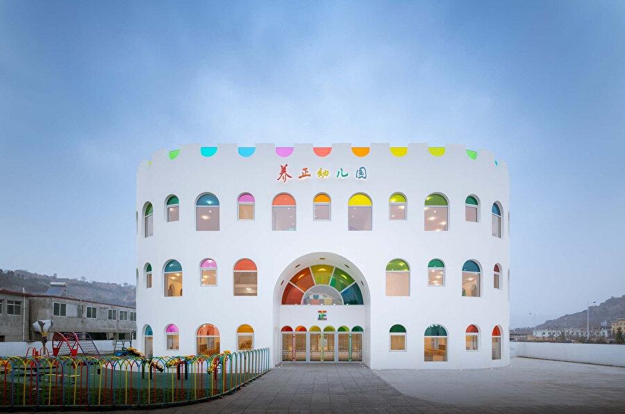 Renkli yarı dairesel pencere açıklıklar, okulun cephesini oluşturuyor.