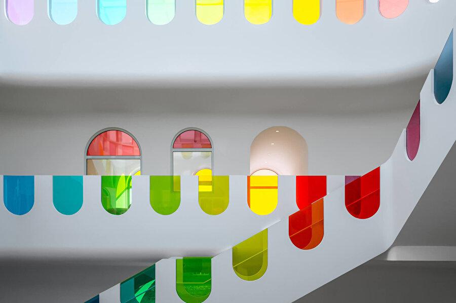 Merdiven boyunca oluşturulan açıklıkları kaplayan polikromatik cam.