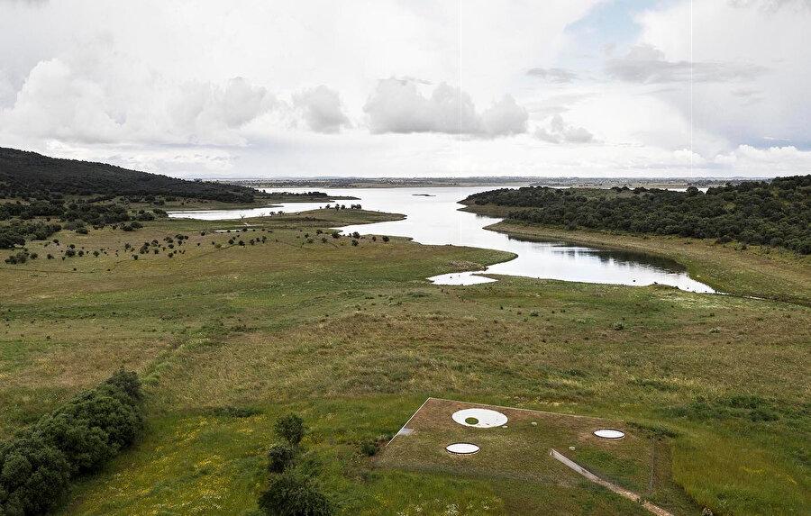 Göle doğru uzanan yeşil çatı, avlu için saçak oluşturuyor.