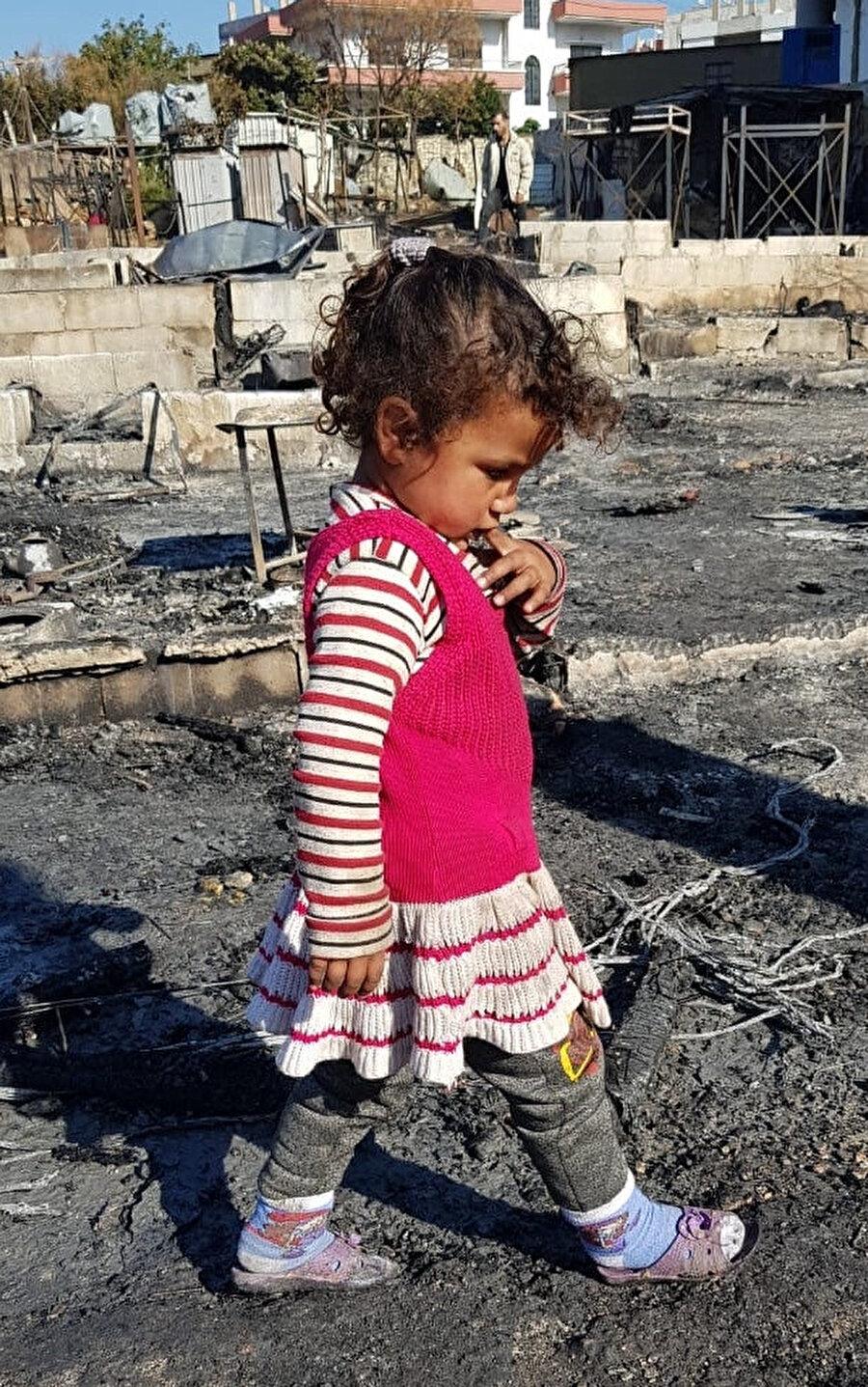 Yangının gerçekleştiği noktada eşyalarını arayan mülteci çocuk.
