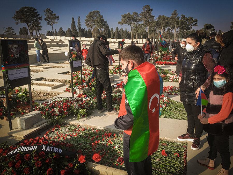 Azerbaycan bayraklarıyla şehitlikleri ziyaret eden binlerce vatandaş, mezarlara çiçek bıraktı, dualar etti.nn