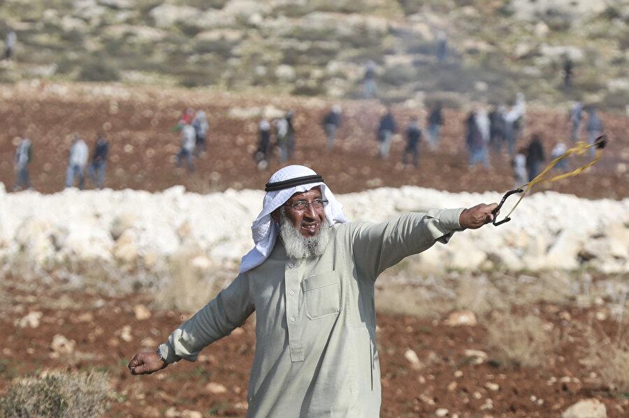 Filistinli Hacı Said Arme, başında puşisi ve kufiyesiyle, üstünde cellabiyesi, beyaz sakalı ve elindeki sapanıyla İsrail askerlerine taş atarken...