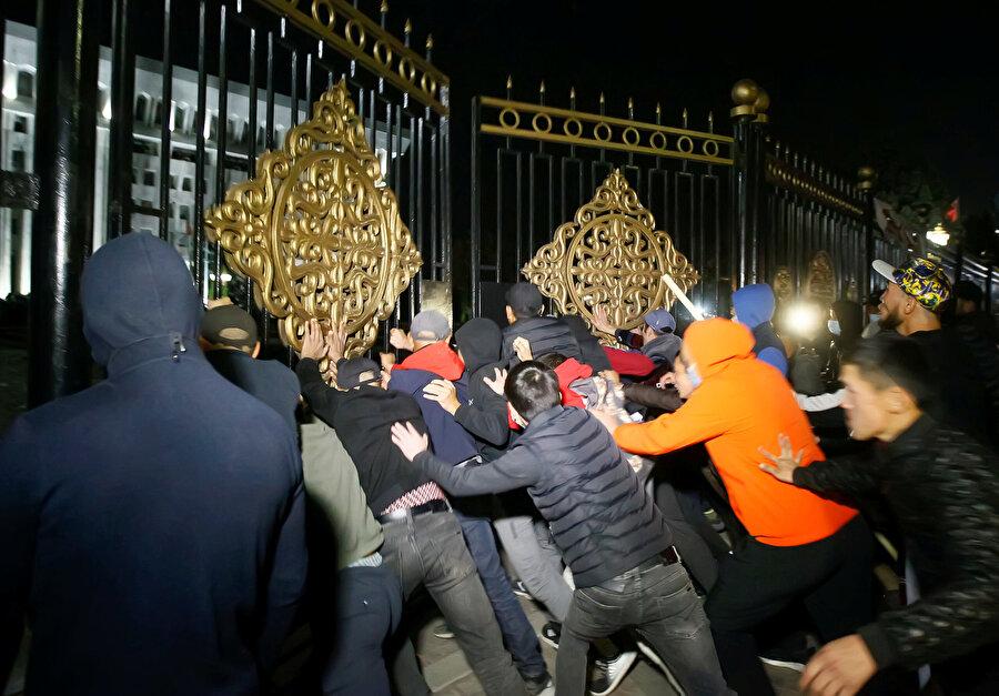 Hükümet binalarının kapılarını zorlayan öfkeli göstericiler.