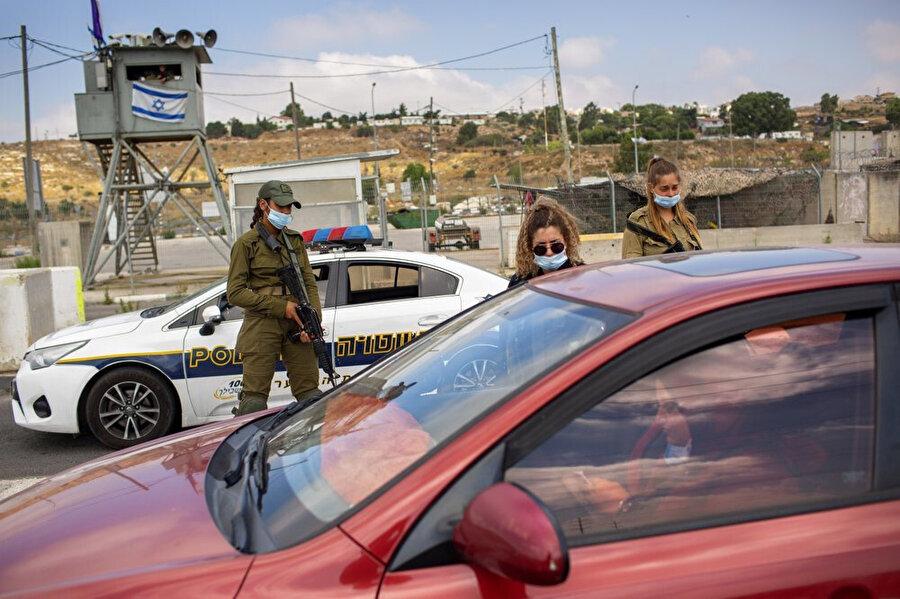 Filistinli bir kadına kimlik kontrolü yapan İsrail askerleri.