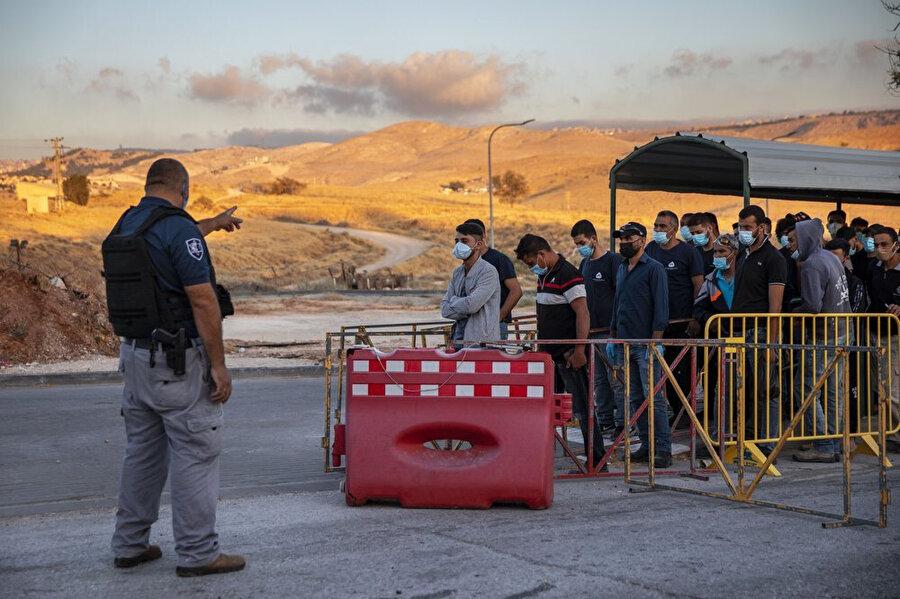 Kontrol noktasında bekletilen Filistinli işçiler.