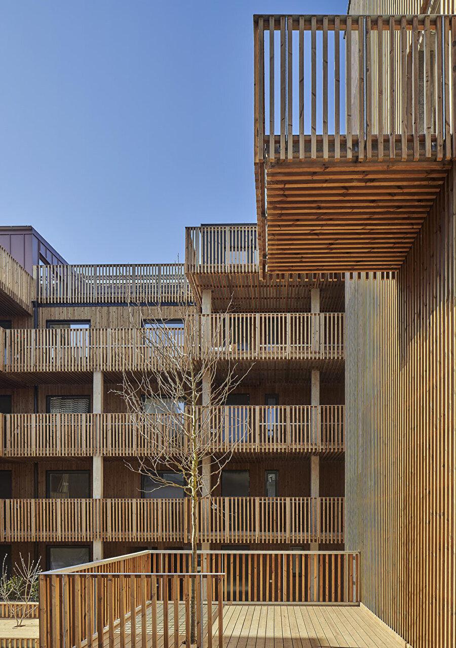 Ortak koridorlardaki küçük balkonlar, sakinler için açık havada oturma alanları oluşturuyor.