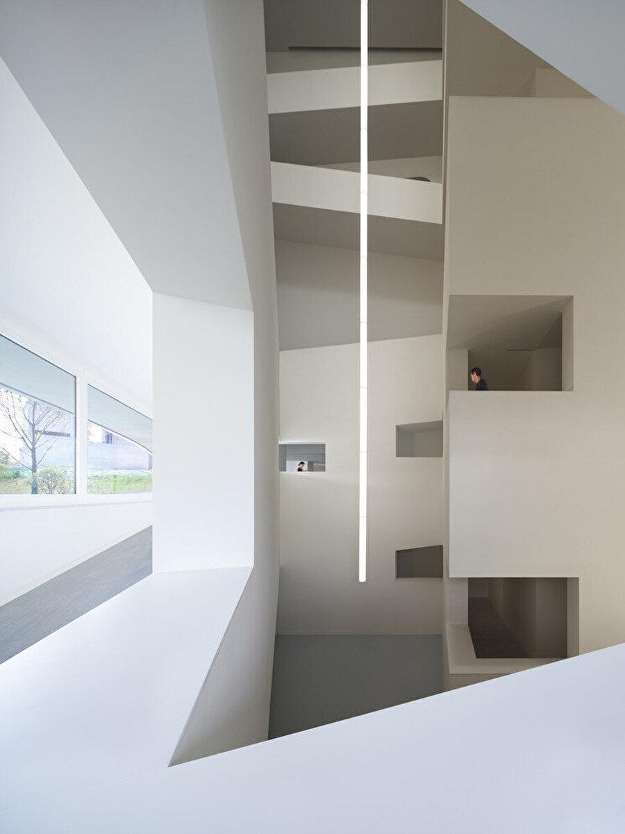 Bina, en altta yer alan bant pencerelerden, doğal ışık alıyor.