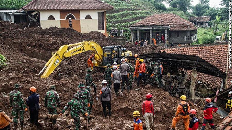 Toprak altında kalanlara ulaşmaya çalışan kurtarma görevlileri.